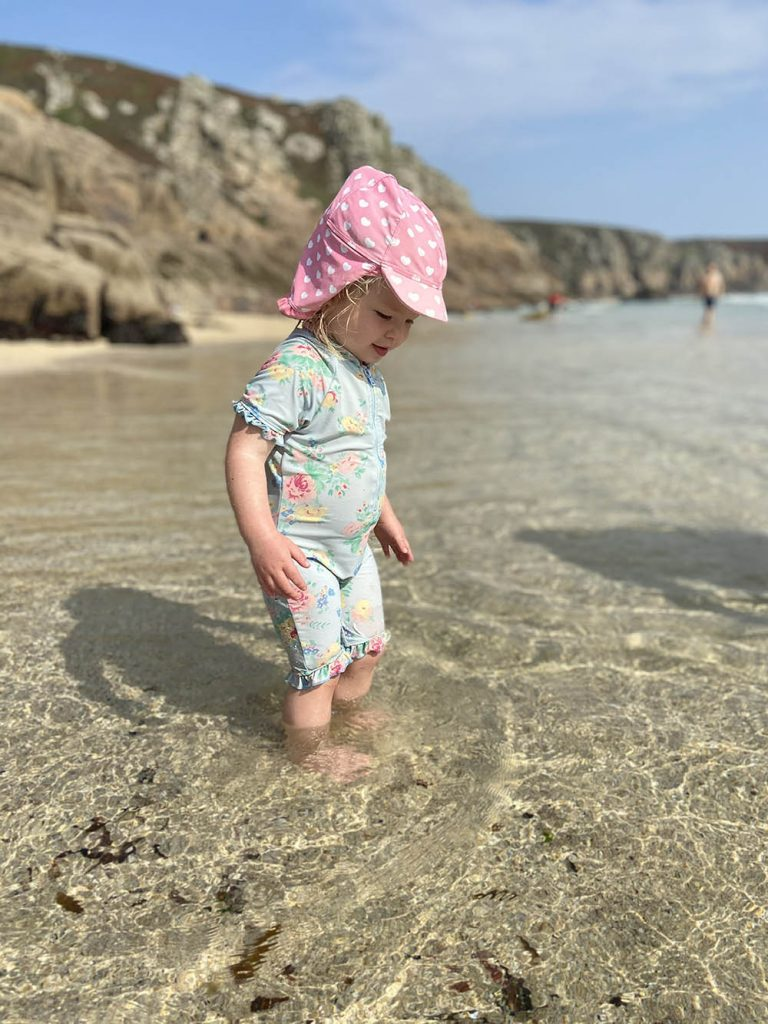 Delilah splashing about in the sea at Porthcurno beach