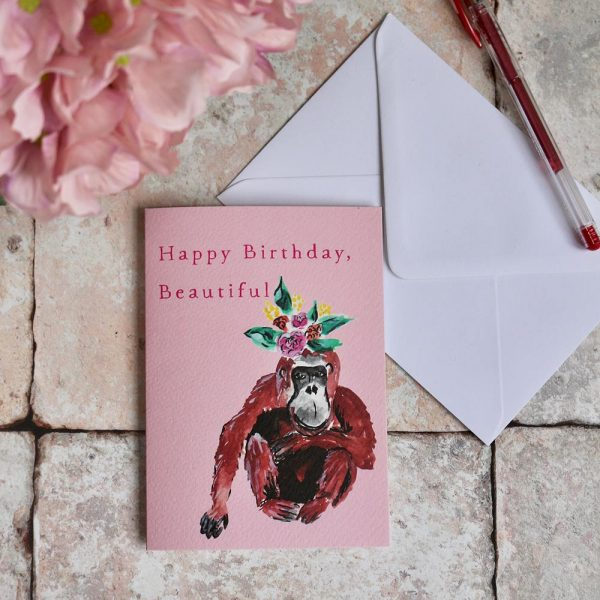 Orangutan birthday card. Greetings card with the phrase Happy Birthday Beautiful. The card is a pastel candy pink colour with a handprinted orang-utan with flowers on it's head. Shown with an envelope, pen and pink hydrangea flower.