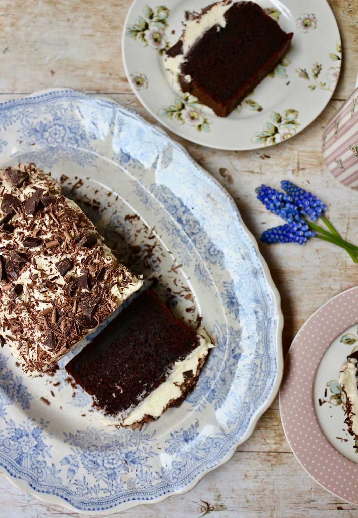chocolate guinness loaf cake on a vintage blue platter with Katie Alice plates and mugs of tea