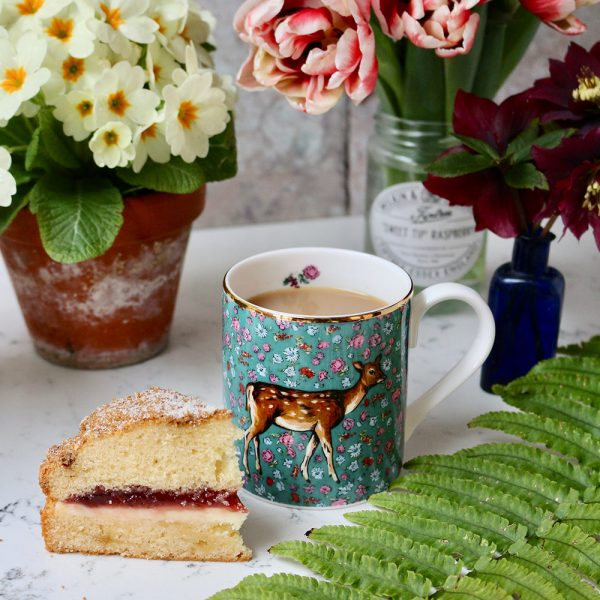 green floral mug with deer motif, filled with tea and with a slice of cake