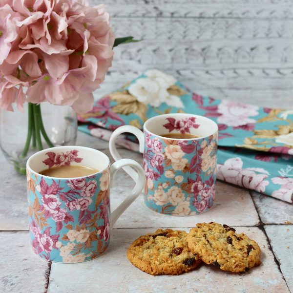 Two of the English roses mugs with the matching tea towel in the background, pink hydrangea and some cheeky biscuits